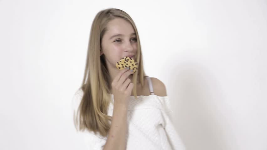 People, happy childhood, food, sweets and bakery concept - smiling little girl eating cookie or biscuit | Shutterstock HD Video #1016943724