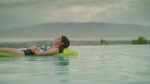 Surface level view of girl floating on pool raft in swimming pool / Cedar Hills, Utah, United States