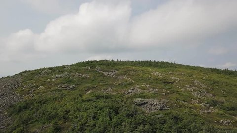 Aerial footage of White Cap Mountain situated within the watershed of the Pleasant River located in Piscataquis County, Maine. It has a distinguished treeline and remains snow covered into summer.