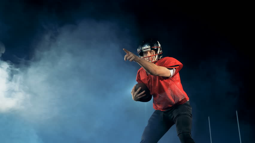 Professional american football player catches a ball while standing on a field. #1016969674
