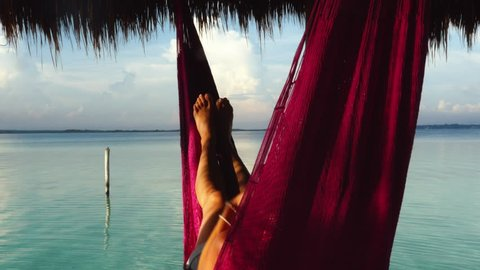 A girl in a hammock watching her smart phone during vacation