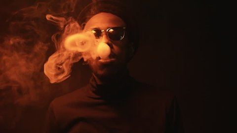 Low-key portrait shot of black man in sunglasses and hat exhaling puffs of  smoke in dark studio with red lighting