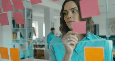 Caucasian female worker standing near glass wall with sticky notes, framework for managing work, scrum methodology. 4K UHD 60 FPS SLOW MOTION