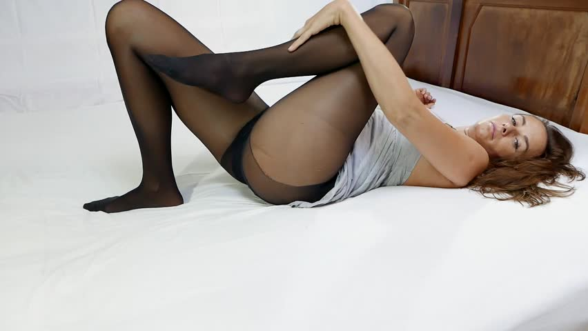 video shoot  attractive model posing in pantyhose  lying on bed