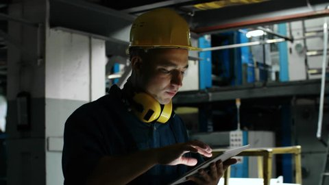 Medium follow shot of concentrated male worker in hard hat walking through factory and using tablet computer