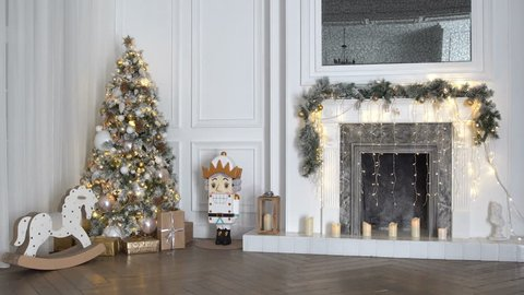 4K footage of white christmas interior with New Year tree decorated with present boxes and gifts, rocking horse, nutcracker and fireplace