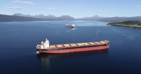 Aerial footage of a cargo ship on the open sea with other ship and mountains in the background, Narvik, Norway