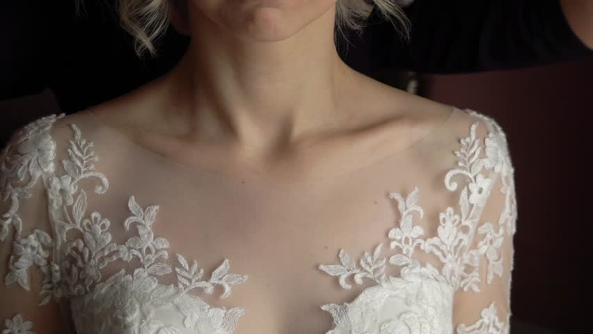 Wedding. Jewelry. The bride in a white dress putting on a necklace around her neck slow motion