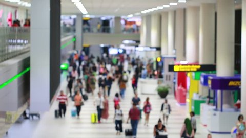 Blurred of crowd many Passenger walking in Suvarnabhumi international airport with carries luggage in terminal for arrive and traveler rental car counter service