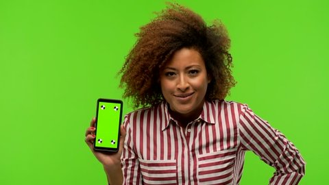 Afro american woman holding phone on green chroma looking forward, scolding someone very angry