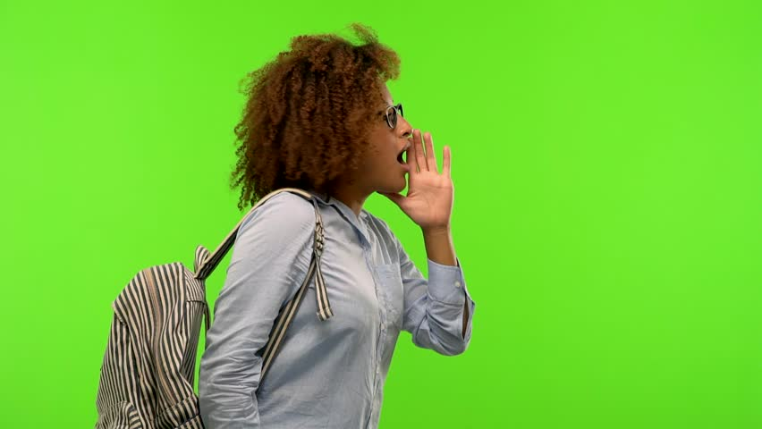 Young afro american student woman on a green chroma screen whispering gossip undertone, trying not to be heard