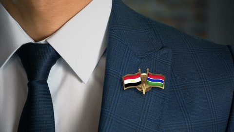 Businessman Walking Towards Camera With Friend Country Flags Pin Egypt - Gambia