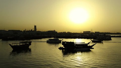 Harbour at sunset in Doha old town, Qatar, Persian Gulf, Arabian Peninsula, Middle East. Doha - capital and most populous city in Qatar. Dhow - traditional wooden Qatari boat