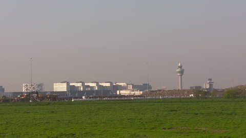 SCHIPHOL, AMSTERDAM AIRPORT - APRIL 2018: Two air traffic control towers and skyline schiphol airport take off aircraft KLM straight up. Late afternoon.