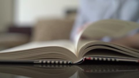 A girl reads a book and turns pages, a close-up, a blurred background