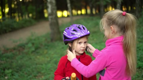 The older sister helps the younger girl to put on a safe helmet before riding a bike on a Sunny summer day in nature and give five to each other.