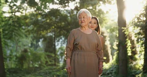 Cheerful panasian granddaughter approaching her mature grandmother, closing her eyes, then hugging and kissing her, then both looking at camera. 4k