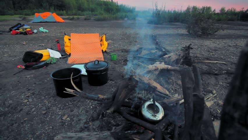 Yukon river, Yukon Territory, Alaska. Night camp of a canoe expedition to Alaska. Kettle boiling on a camp fire.