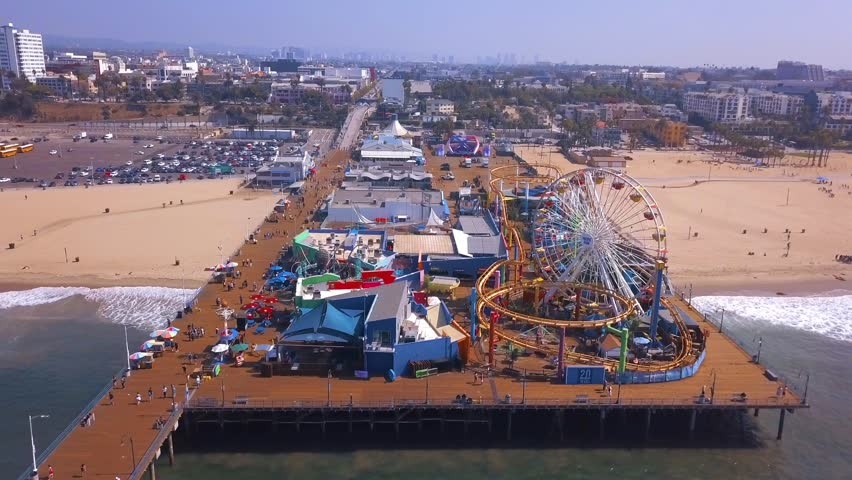 Early morning aerial view of the Santa Monica pier during a sunny day with amusement park view and people walking around in Los Angeles.