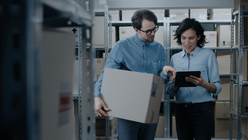 Female Inventory Manager Shows Digital Tablet Information to a Worker Holding Cardboard Box, They Talk and Do Work. In the Background Stock of Parcels with Products Ready for Shipment.  | Shutterstock HD Video #1017422854