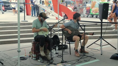New York, United States - jun 22, 2016: Street musicians play country music in New York City, United States. Street artist plays electric guitar live in busy city street. Video with ambient sound.
