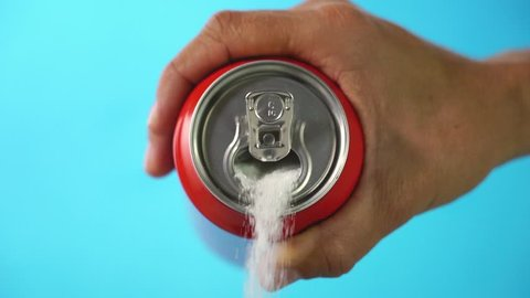 Red soda can pouring out white sugar on a bright blue background showing an example of how bad sugar and how we all eat to much sugar in health food concept. Slow motion