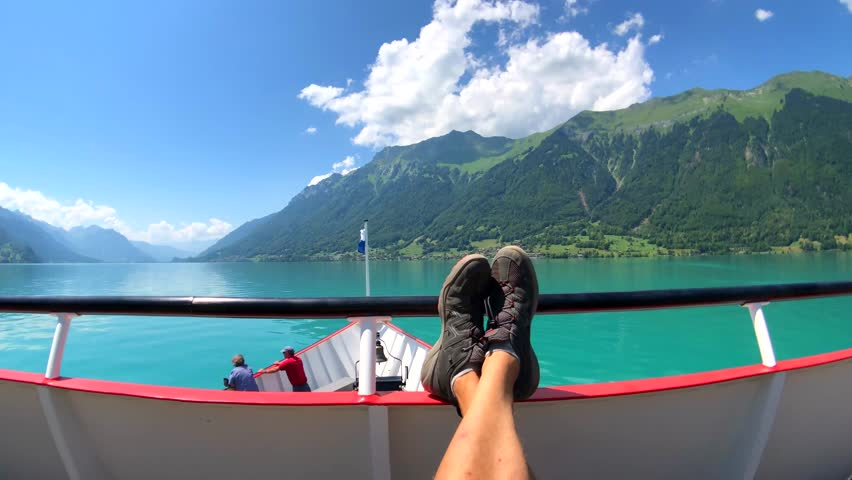 POV travelling by boat at Brienz lake at summer time in Switzerland. Tourists feet at foreground | Shutterstock HD Video #1017456694