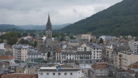 Aerial view. Town of Lourdes, Hautes Pyrenees, France. Looking east. View of Rue Lafitte and Catholic church Paroisse de Lourdes. Handheld shot with stabilized camera.