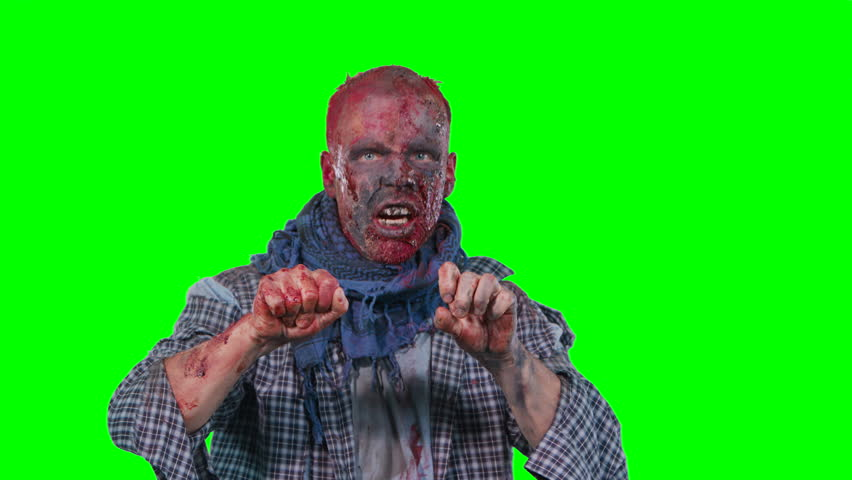 Halloween theme horrible scary zombie in clothes breaks out of the bottom of the screen and want to catch you isolated over green screen background | Shutterstock HD Video #1017467524