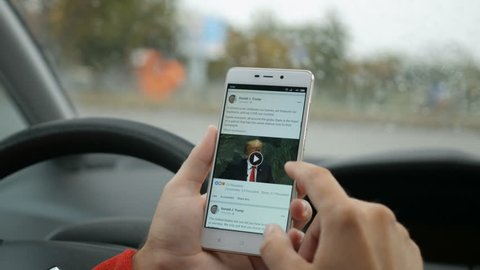 Man using his smartphone with to scroll Official facebook profile of president of USA Donald Trump feed, scrolling news. Driver reads news on mobile phone inside car. New York - September 2018