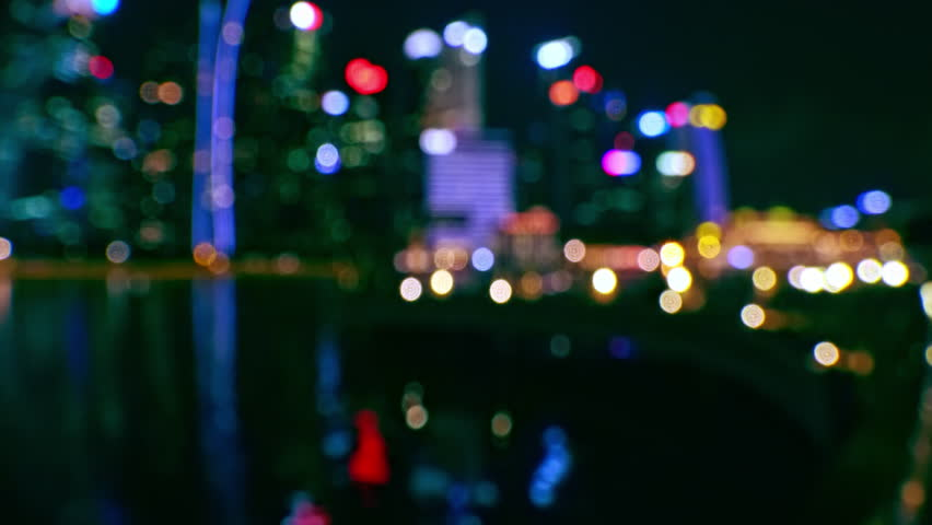 Unfocused view of Singapore city from pier at nighttime. Blurred night cityscape with buildings of modern architecture reflecting in sea. Amazing skyscrapers and their water reflection in darkness. | Shutterstock HD Video #1017517924