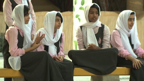 SHARJAH, UAE - CIRCA SEPTEMBER 2014: group of Arab teenage girls walking in school uniform empowered by increased opportunities for women in the United Arab Emirates