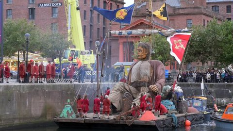 Liverpool, Merseyside,England,Uk. October 5th, 2018.  'Liverpool Giants' Puppet Show By Royal De Luxe. Giant puppet sailing on a floating raft , assisted by Lilliputians at the Albert Dock, Liverpool.