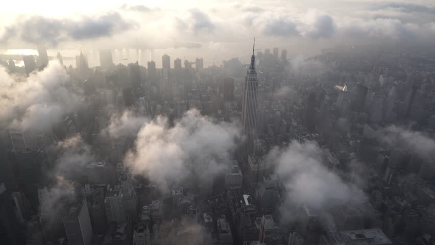 New York City Circa-2015, aerial view approaching the Empire State Building at sunrise, with Midtown Manhattan skyscrapers under low level clouds and fog