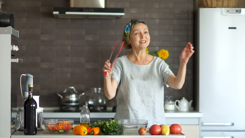 Well-groomed, beautiful middle-aged woman pensioner dancing in the kitchen with a red spatula for frying. Bright kitchen interior, on the table are vegetables. Happy secured pension