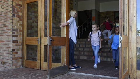 Smiling elementary school children happy to go home. Joyful school girls and boys wearing backpack and running outside the school at the end of the lessons. Teacher holding door while students running