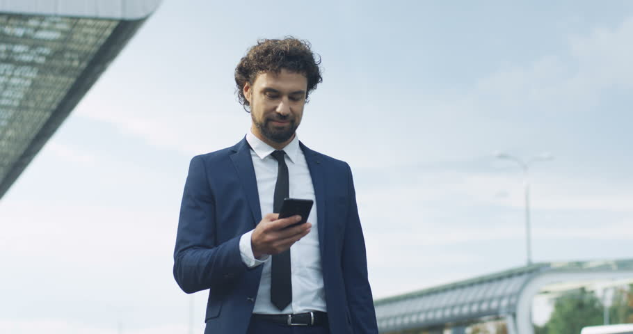 Caucasian young attractive man in the suit and tie standing outside big urban building and answering his moile phone ringing with a smile. | Shutterstock HD Video #1017627784