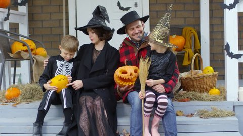 Happy parents and little daughter and son in Halloween costumes holding jack-o-lanterns while sitting on decorated porch and smiling at camera