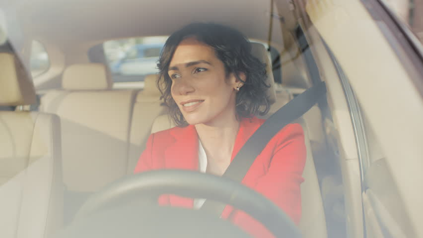 Portrait of beautiful Young Woman Driving Car through big Sunny City. Camera Shot Made From the Front Windshield. | Shutterstock HD Video #1017759634
