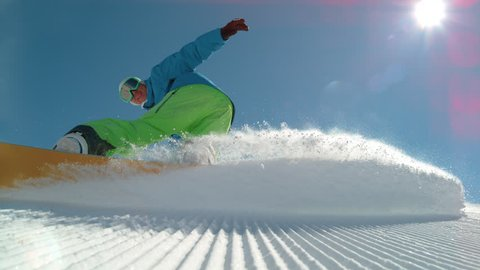 SLOW MOTION, LOW ANGLE, LENS FLARE: Cheerful young male snowboarder carving a freshly groomed slope in the winter sun. Cool shot of snowboarder doing a cool hand drag while riding in the sunny Alps.