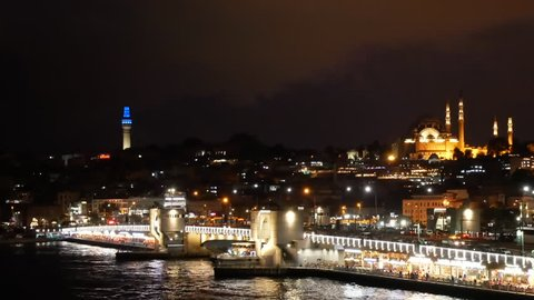 Scenic view at night Istanbul with Galata Bridge and Suleymaniye Mosque with beautiful backight. Ferry sails on Golden Horn gulf under Galata Bridge. 4k video footage