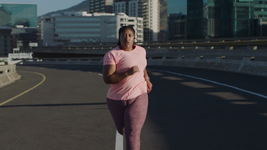 fat woman running exercising intense weight loss workout jogging in urban city background at sunrise committed fitness lifestyle #1017906754