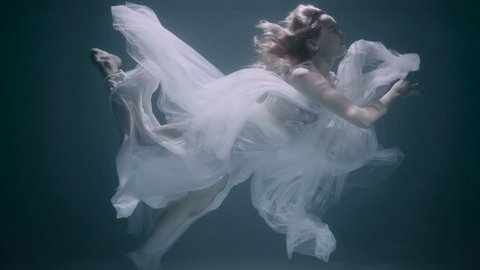 Young girl in a white dress swimming under the water.