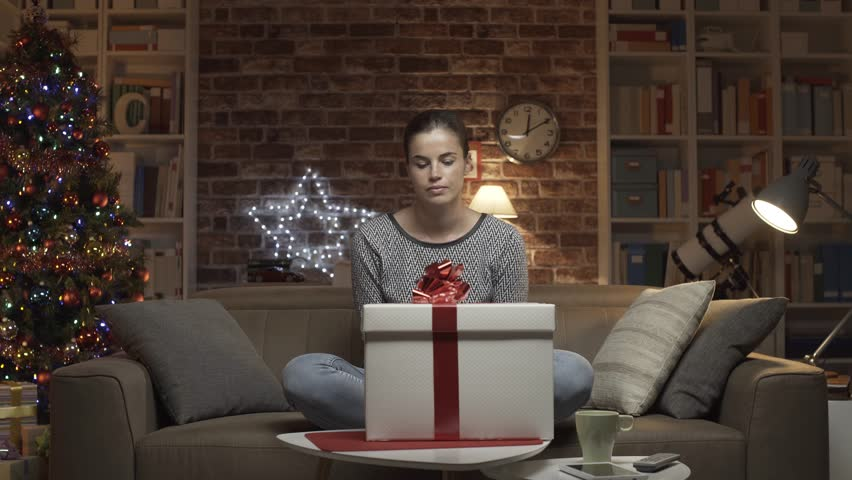 Disappointed woman receiving a bad Christmas gift at home, she opens the box and finds a pair of ugly slippers | Shutterstock HD Video #1017930184