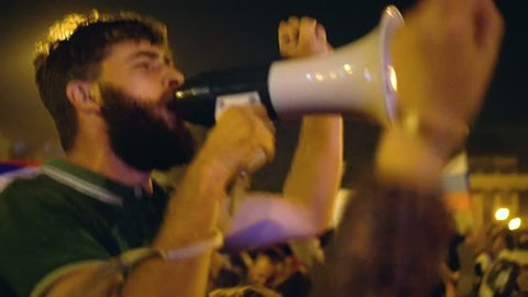 A young guy comes out from the loudspeaker for the crowd against the current government. A man jumps and lights the crowd at the right atmosphere. In the night city the activist conducts a strike.