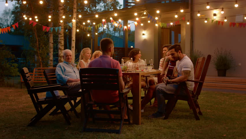 Sitting at the Dinner Table Handsome Young Man Plays the Guitar For a Friends. Family and Friends Listening to Music at the Summer Evening Garden Party Celebration. | Shutterstock HD Video #1018015894
