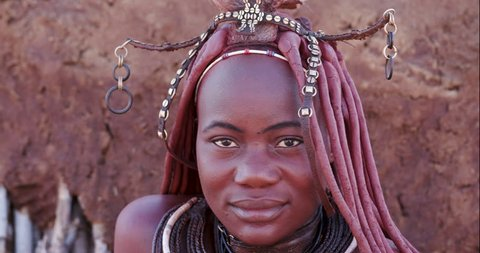 4K close-up portrait view of a pretty Himba girl showing head gear and neck jewellery, and looking into camera,Namibia