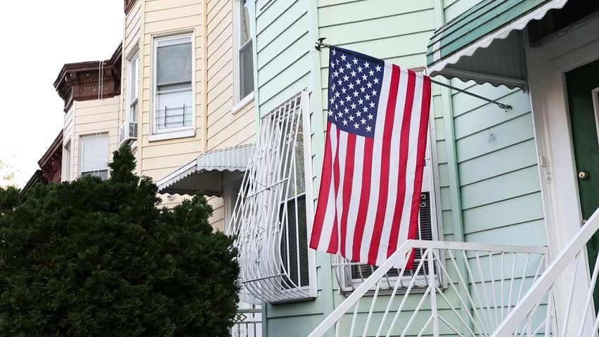 Flag Of The United States Of America. The flag flutters near the entrance to the house | Shutterstock HD Video #1018093504