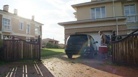 Panning wide shot of family preparing to go on picnic. Man and woman with basket and electric cooler and children with blanket and umbrella loading things into trunk of car parked in front of house