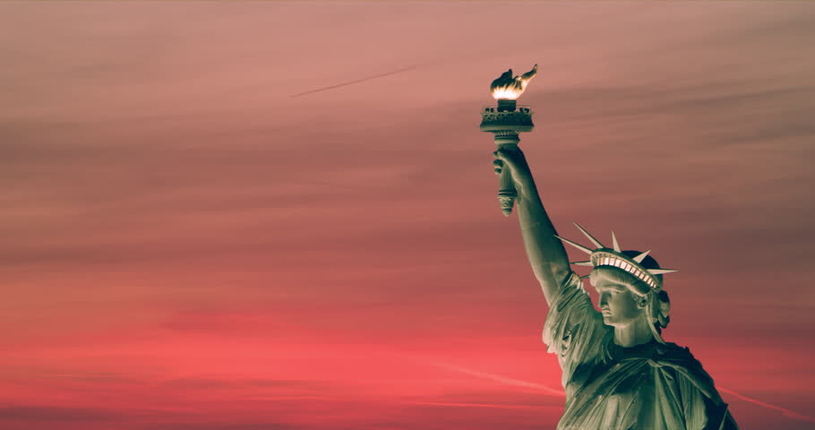 Aerial view of the Statue of Liberty at sunset, New York City, bright light. Medium to wide shot.